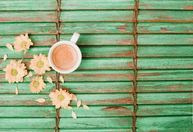 I fiori si avvicinano alla tazza di caffè su fondo di legno