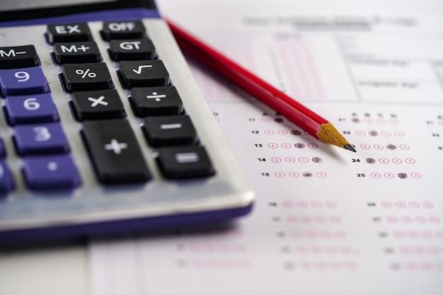 I fogli di risposta con il disegno a matita riempiono per selezionare la scelta e il calcolatore