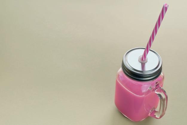I frullati freschi naturali bevono in tazza di vetro con paglia su fondo grigio chiaro.