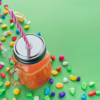 I frullati freschi naturali bevono in tazza di vetro con paglia su fondo verde.