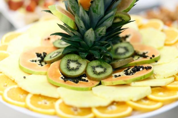 I frutti esotici tagliati in cerchio giacciono sul piatto rotondo della cena