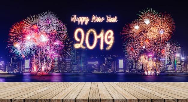 I fuochi d'artificio del buon anno 2019 sopra paesaggio urbano alla notte con la tavola di legno vuota della plancia