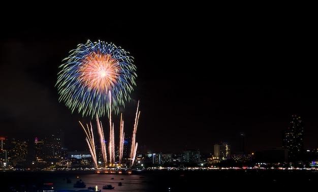I fuochi d'artificio hanno esplorato sopra paesaggio urbano alla notte in porto marittimo a pattaya.