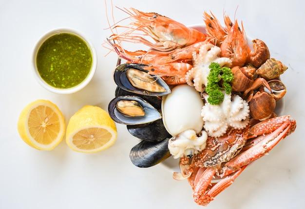 I gamberi freschi i calamari i calamari hanno avvistato il limone della salsa di frutti di mare e del granchio dei crostacei di babilonia sul fondo di bianco del piatto.