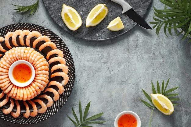 I gamberi piccante di limone e aglio sono serviti su un piatto scuro con limoni e salsa di peperoncino dolce, piatto su sfondo scuro