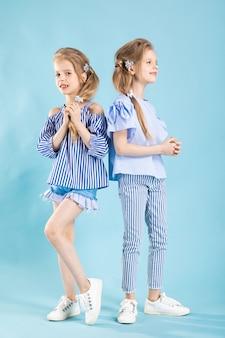 I gemelli delle ragazze in vestiti blu-chiaro stanno posando su una parete blu.
