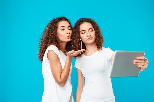 I gemelli di due womans che fanno selfie sulla compressa sopra il blu.