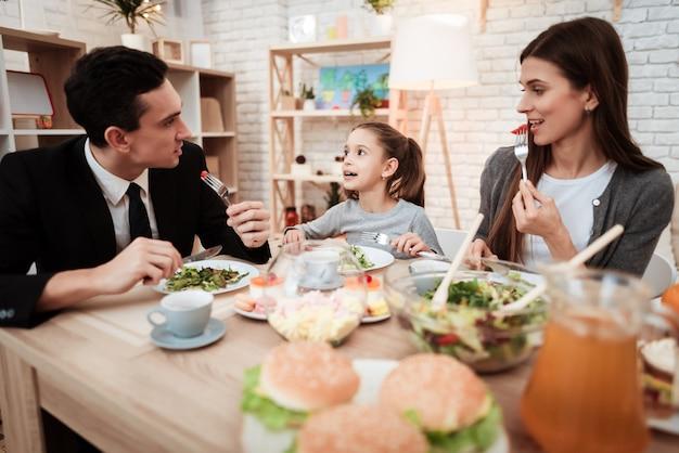 I genitori con la loro figlia si sono riuniti a tavola