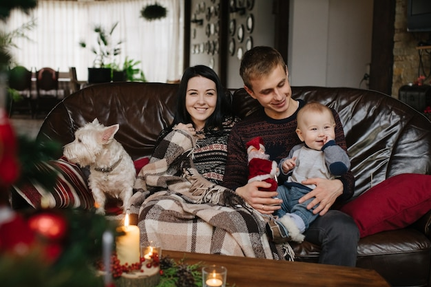 I genitori con un bambino a natale e un cane seduto sul divano