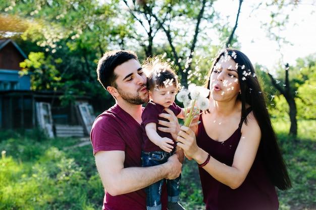 I genitori con un bambino in braccio che soffia denti di leone