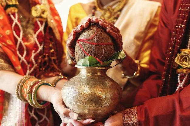 I genitori della sposa indiana tengono una ciotola con cocco sotto le sue mani