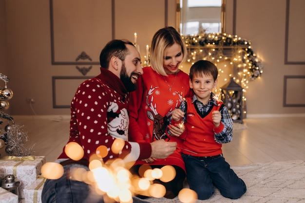 I genitori e il loro figlioletto in maglione rosso si divertono con i fuochi del bengala seduti