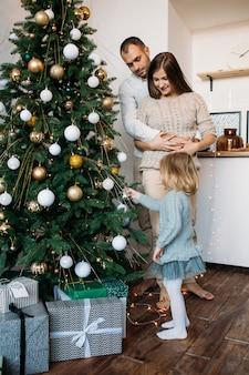 I genitori e la figlia decorano l'albero di natale in casa