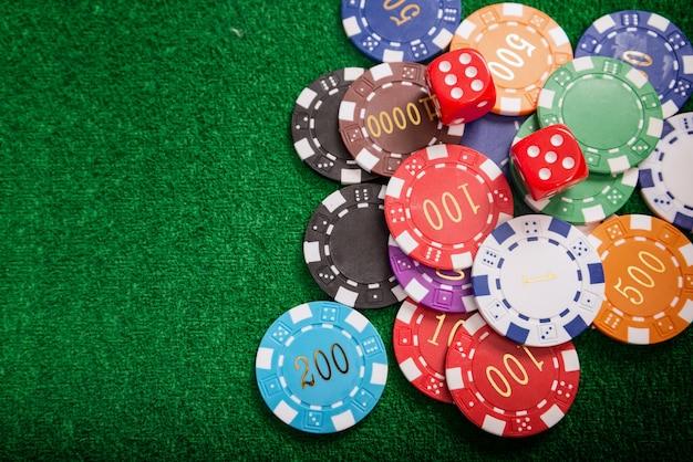 I gettoni dei casinò colorati posizionati sul tavolo verde sono monete che vengono usate per scommettere in casin