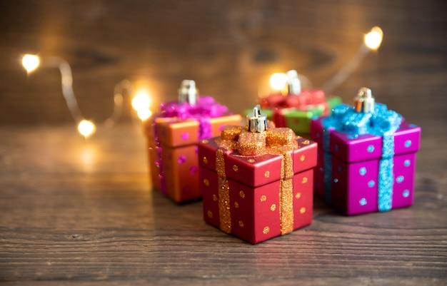 I giocattoli del nuovo anno sotto forma di scatole regalo stanno su un vecchio tavolo di legno. concetto di natale e capodanno.