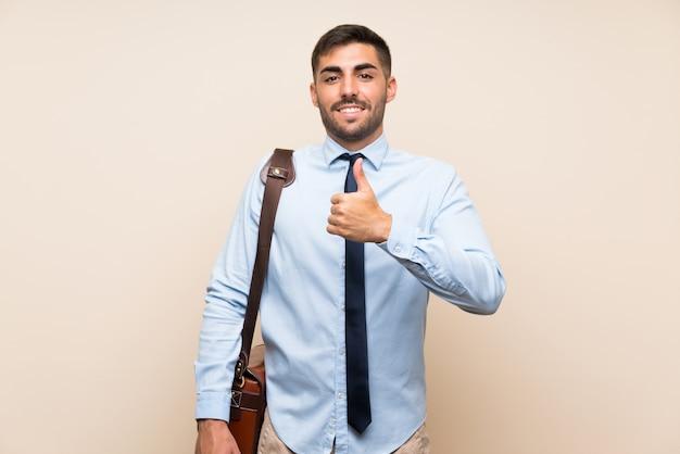 I giovani affari con la barba sopra la parete isolata che dà un pollice in su gesticolano