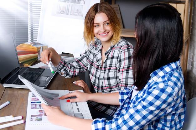 I giovani architetti arredatori che lavorano come freelance sviluppano un nuovo progetto di appartamento nello studio di design. una riunione femminile della ragazza di due donne con lo scrittorio di raduno con il pin up schizza i disegni e le bozze di nuovo progetto