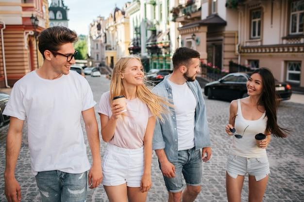 I giovani camminano insieme per la strada e parlano tra loro