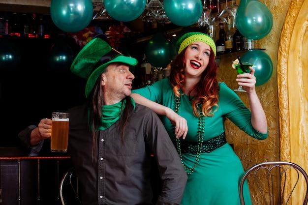 I giovani celebrano il giorno di patrick divertente bar bar carnevale copricapo ragazza uomo birra cocktail vestiti verdi cappello sorriso bellissimo leprechaun