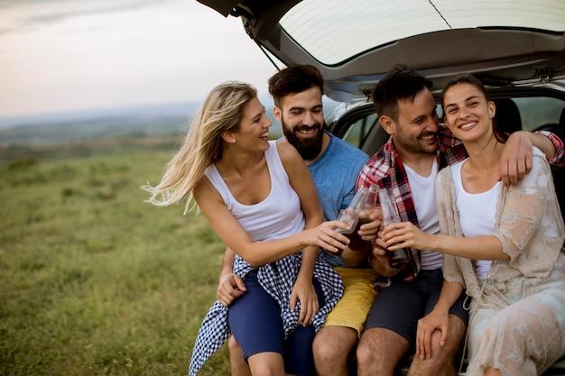 I giovani che si siedono nell'automobile trank durante il viaggio nella natura