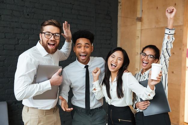 I giovani colleghi emozionanti felici di affari fanno il gesto del vincitore.