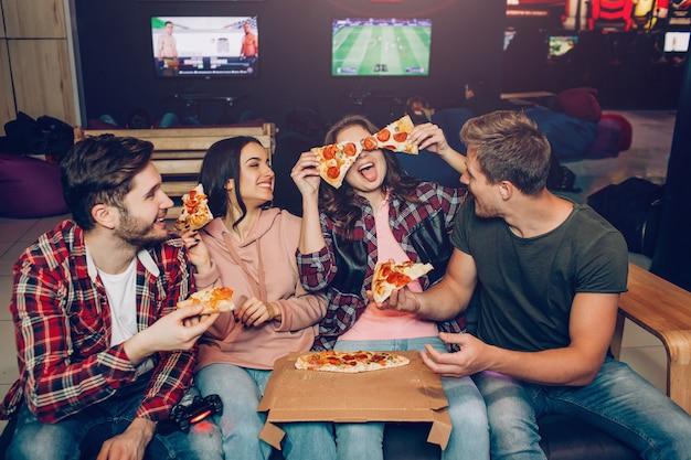I giovani divertenti si siedono insieme nella sala e mangiano la pizza. giocano con i suoi pezzi. compagni di squadra che ridono.