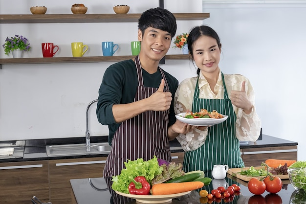 I giovani e le ragazze asiatiche stanno mostrando l'insalata di gamberi