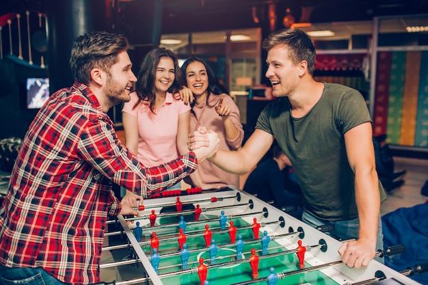 I giovani felici stanno al calcio balilla nella stanza da gioco e si tengono per mano. hanno competizione. le giovani donne stanno dietro e le guardano.