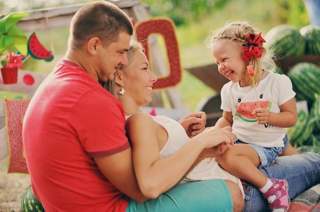 I giovani genitori giocano con un bambino piccolo in giardino