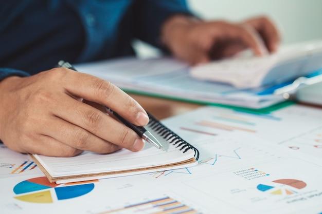 I giovani imprenditori calcolano e analizzano i grafici di mercato, calcolatori degli uomini d'affari per calcolare costi e profitti. una buona pianificazione del marketing deve essere prudente. con analisi dalle statistiche dei grafici.