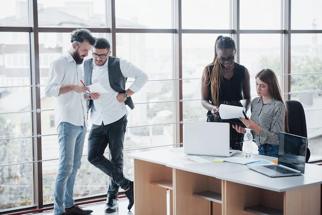 I giovani imprenditori stanno discutendo insieme nuove idee creative durante una riunione in ufficio