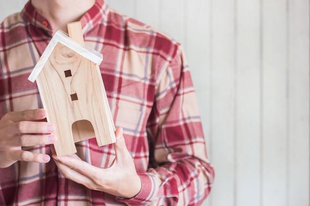 I giovani indossano la camicia rossa del percalle che tiene il modello miniatura della casa, il concetto di investimento della proprietà, copyspace