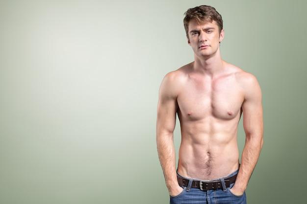 I giovani misura l'uomo topless nella posa delle blue jeans