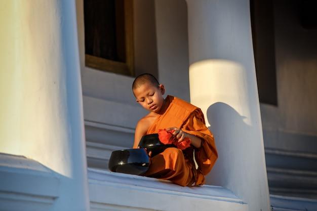 I giovani monaci del principiante si siedono pulendo la ciotola delle elemosine in monastero il tempio della grande finestra