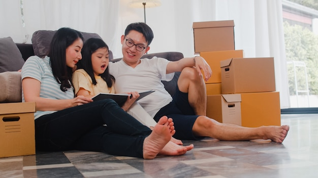 I giovani proprietari di case asiatici felici hanno comprato la nuova casa. mamma cinese, papà e figlia che abbracciano in attesa del futuro nella nuova casa dopo essersi trasferiti nella delocalizzazione seduti insieme sul pavimento con le scatole.