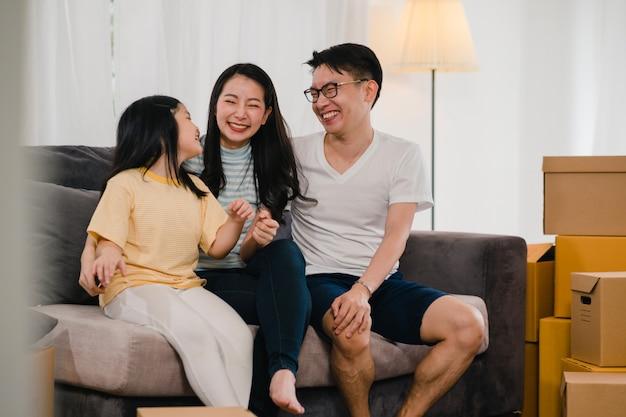 I giovani proprietari di case asiatici felici hanno comprato la nuova casa. mamma, papà e figlia giapponesi che abbracciano in attesa del futuro nella nuova casa dopo essersi trasferiti nella delocalizzazione che si siede insieme sul sofà con le scatole.