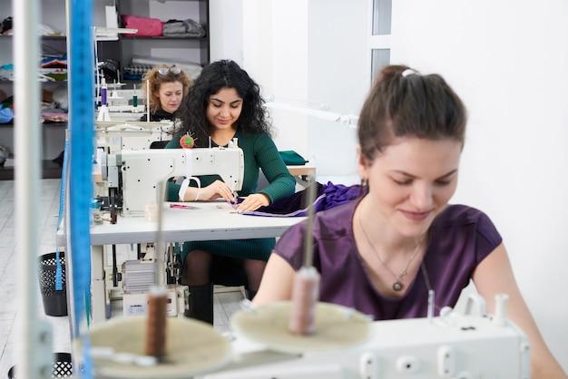 I giovani sarti cucono i vestiti sulla macchina per cucire nello studio dell'atelier