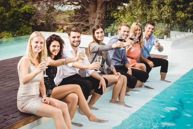 I giovani seduti a bordo piscina, bevono, si divertono, si godono le vacanze