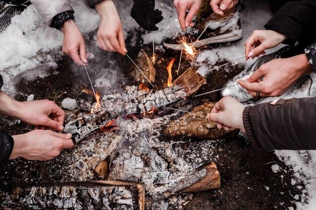 I giovani seduti attorno al fuoco nella foresta in inverno e le luci del bengala in fiamme