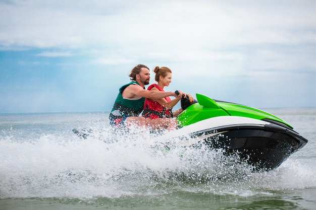I giovani si divertono a guidare ad alta velocità su scooter d'acqua, uomo e donna in vacanza estiva, amici che fanno sport attivo
