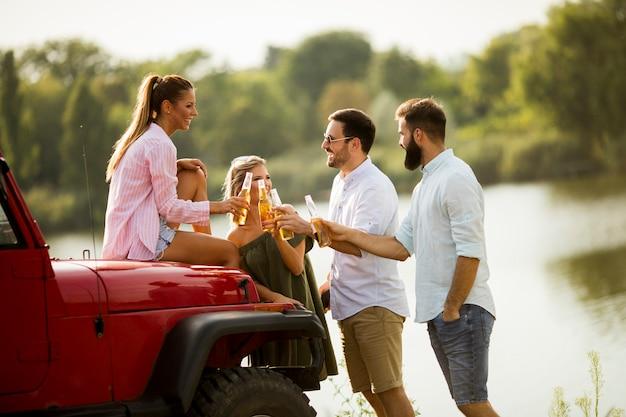 I giovani si divertono in auto convertibile dal fiume
