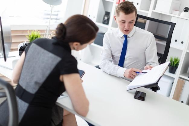 I giovani si siedono in ufficio al tavolo del computer e lavorano con i documenti.
