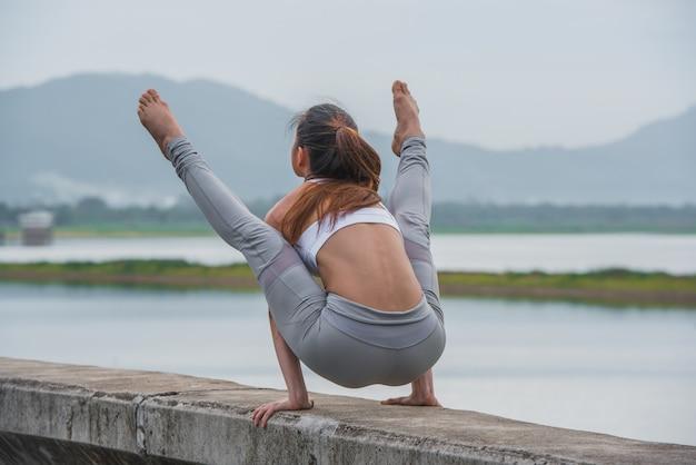 I giovani sport donna che fa l'yoga sul lago con sfondo di montagna.