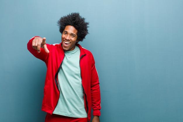 I giovani sport neri equipaggiano indicare alla macchina fotografica con un sorriso soddisfatto, sicuro, amichevole, scegliendovi contro la parete del grunge