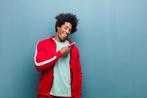 I giovani sport neri equipaggiano sembrare eccitato e sorpreso indicando il lato e verso l'alto per copiare lo spazio