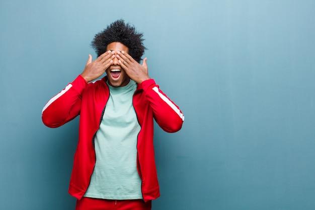 I giovani sport neri equipaggiano sorridere e sentirsi felici, coprendo gli occhi con entrambe le mani e aspettando un'incredibile sorpresa contro la parete del grunge