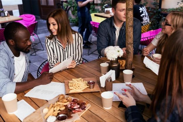 I giovani stanno ordinando cibo sulla terrazza di un caffè e discutendo di lavoro e piani futuri