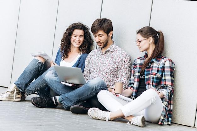 I giovani stanno usando gadget differenti e sorridenti, seduti vicino alla parete. studenti che studiano utilizzando computer portatile. concetto di social media di educazione.