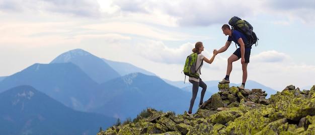 I giovani turisti con gli zaini, ragazzo atletico aiuta la ragazza esile a clime la cima rocciosa della montagna contro il cielo luminoso dell'estate e il fondo della catena montuosa. concetto di turismo, viaggi e stile di vita sano.