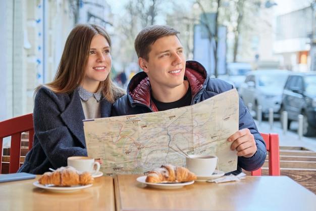 I giovani turisti equipaggiano e donna che legge la mappa della città in caffè all'aperto